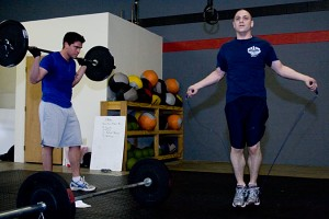 Dan knocking out some double unders while JP just hangs out with the barbell on his back